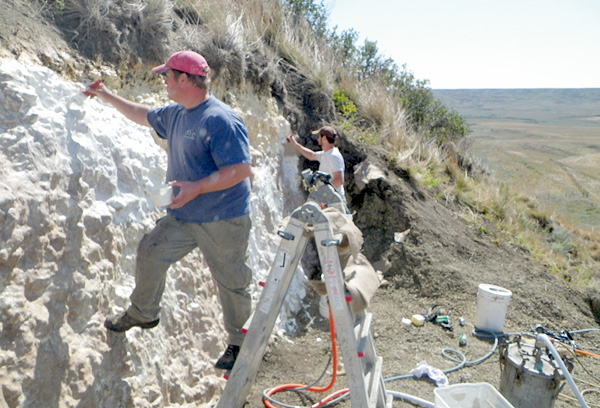 Two men paint moulding material on the sedimentary rock face.