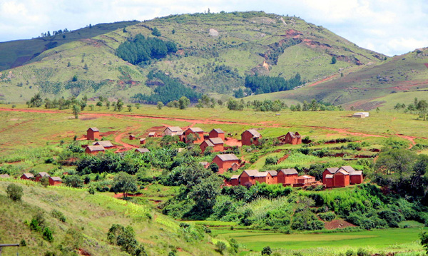 A cluster of reddish buildings amid green fields and hills.