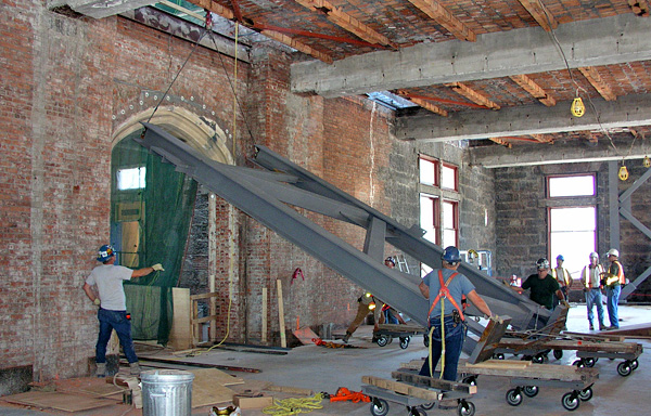 Installation of a steel structural frame in a gallery under renovation.