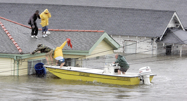 A motorboat near the eaves of a house, with three people in the boat and two people on the roof.