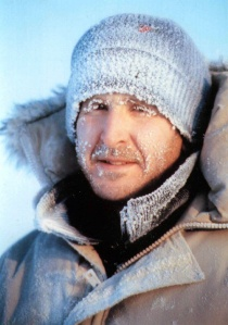 A man in winter coat and hat, his clothing and facial hair covered by frost.