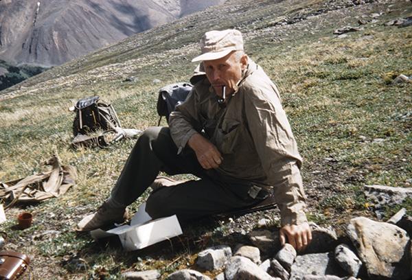 Alf Erling Porsild sits on a rocky slope.