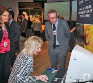 A seated woman uses the computer for the Canadian Disaster Database kiosk in the Nature Unleashed exhibition.