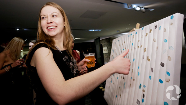 A woman placing her thumbprint on the art piece.
