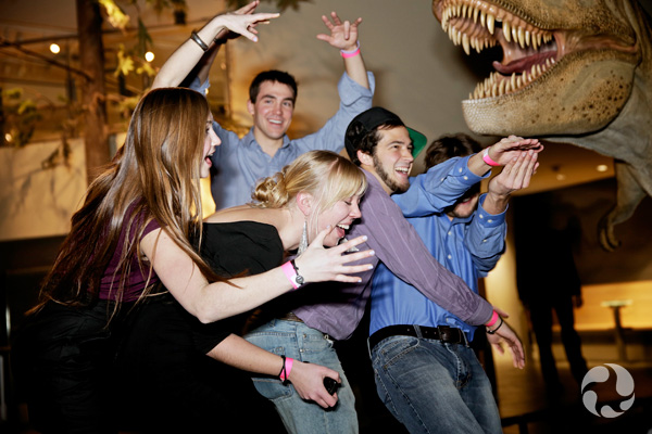 A handful of people in a cluster near a life-sized dinosaur model, making large gestures.