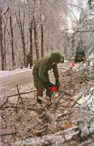 A soldier uses a chain saw to cut a tree that has fallen on ground.