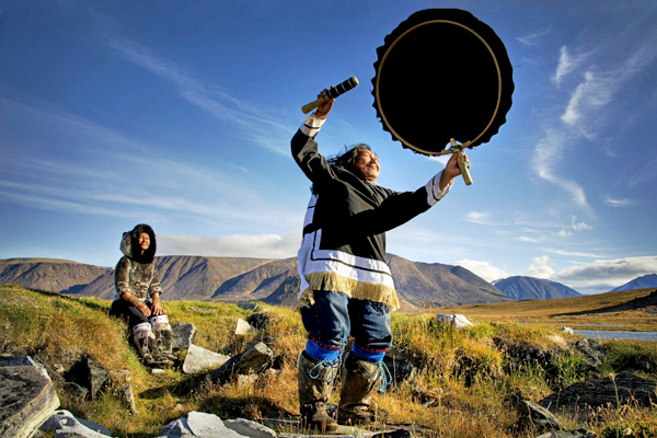 A person holds an Inuit drum overhead in a tundra landscape of hills, plants and water, while another person sits in the background.