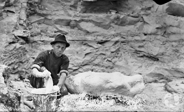 A man squats in front of a rock face, lifting a wet plaster-covered cloth from a bucket beside a plaster field jacket.