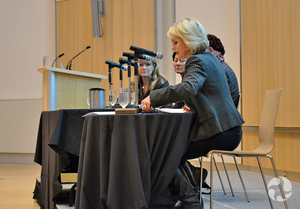 The panellists sit at a table with microphones.