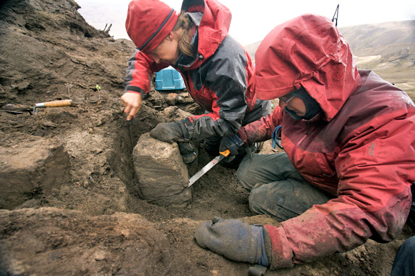 Two women work in a cavity dug out of a barren slope.