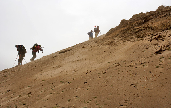 Four people climb a steep slope.