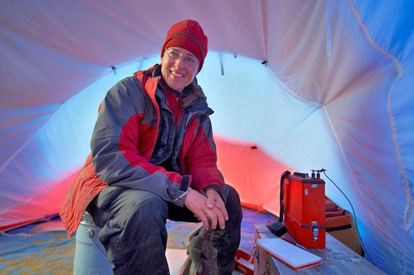 Natalia Rybczynski sits inside a tent with a satellite radio beside her.