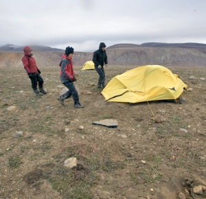 Three people approach a flattened tent in a rocky landscape.