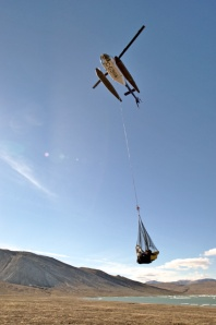 A small helicopter with a net of cargo suspended beneath.
