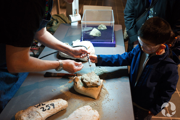 A boy holds an air scribe to a fossil with help from an adult.