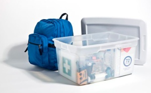 A backpack and clear plastic box containing  emergency items.