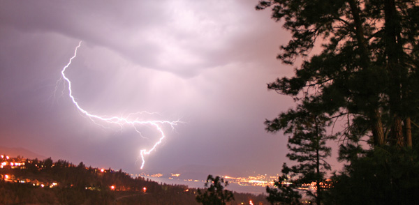 Photo of a lightning bolt in the night sky over forest fires near Kelowna, B.C.