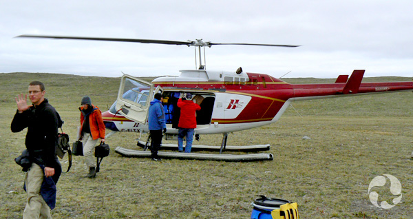 Four people unload gear from a helicopter.