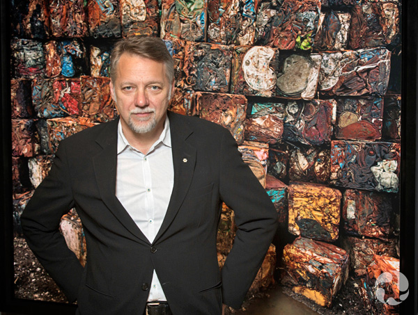 Edward Burtynsky in front of his photo of oil drums.