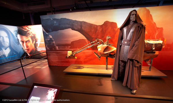 A model of Anakin Skywalker beside a model of a speeder bike.