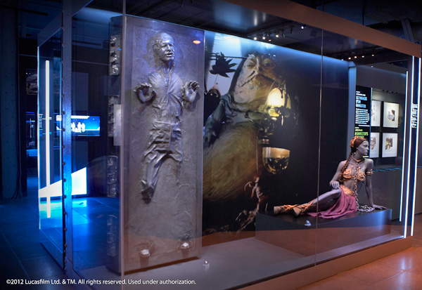 A model of Han Solo in carbonite beside a model of Princess Leia and a photo of Jabba the Hut.