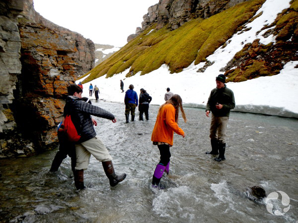 A group of people cross a stream in a canyon.
