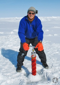 A man stands on snow and uses an ice corer.
