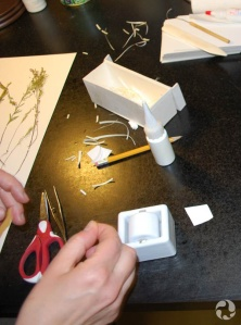 A woman's hands on a table amid assorted plant-mounting tools.