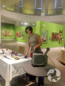 A woman arranges art supplies on a table, beside a film projector in the exhibition.