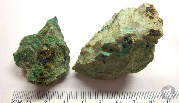 Specimens of mrazekite and hechtsbergite on a table, beside a ruler that indicates their size.