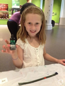 A girl holds a bottle of ink at a table in the gallery.