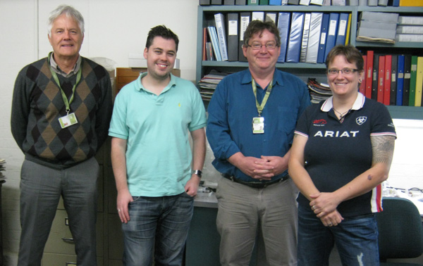 Four people stand in front of a desk.