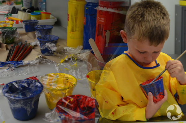 Collage of two images: Cups containing paint and paintbrushes on a table, and a boy painting a plastic glass.