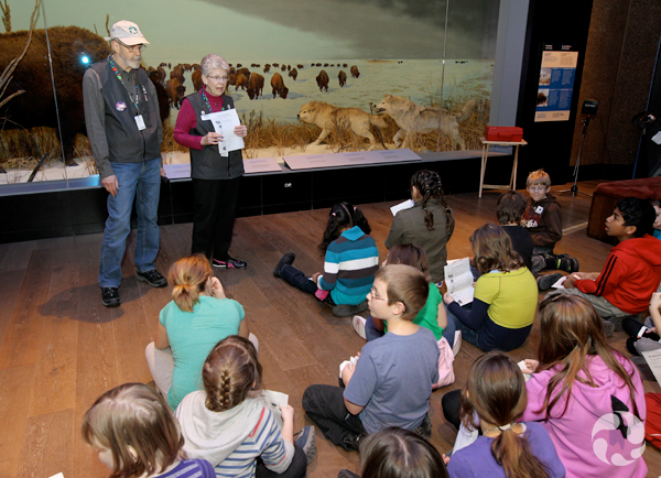 Two adults stand facing many children seated on the floor in front of a mammal diorama.