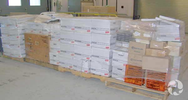 Stacks of boxes containing the Steele collection sit on wooden pallets.