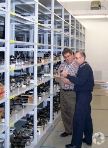 Jean-Marc Gagnon and a volunteer stand beside a shelving unit in the museum's collections.