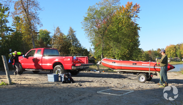 A pick-up truck with a boat on a trailer, boxes of equipment and two men.