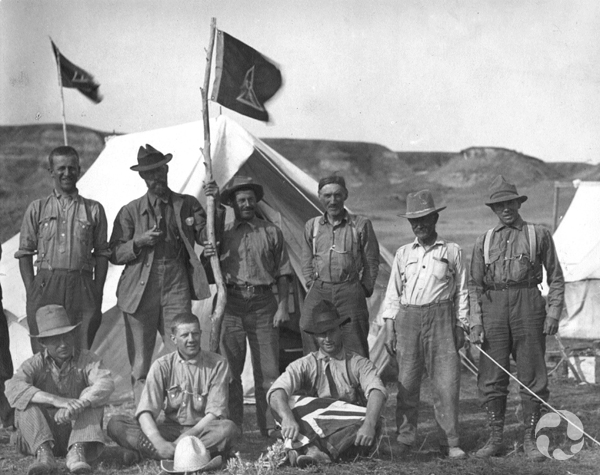 Nine men sit and stand for the camera at a field camp site in Alberta.