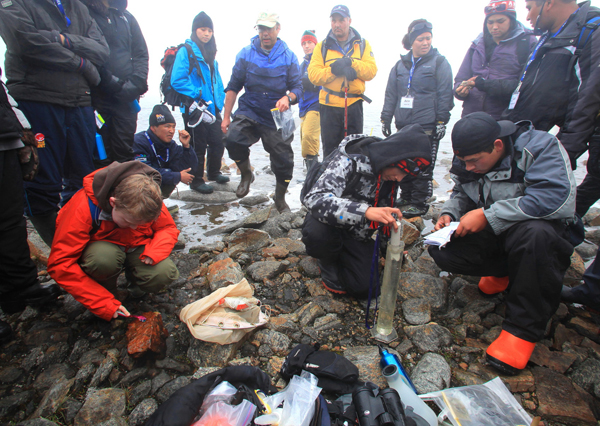 Paul Hamilton supervises students collecting water samples from an Arctic stream.