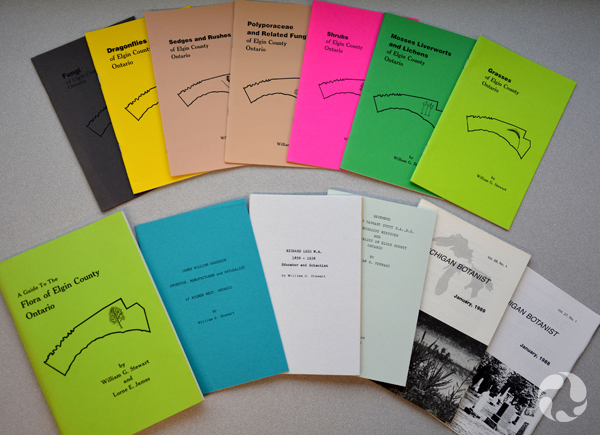 Thirteen booklets arranged on a table.