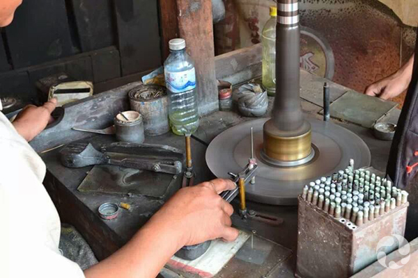A gem cutter holds a stick holding a zircon as he sits at table with cutting device.