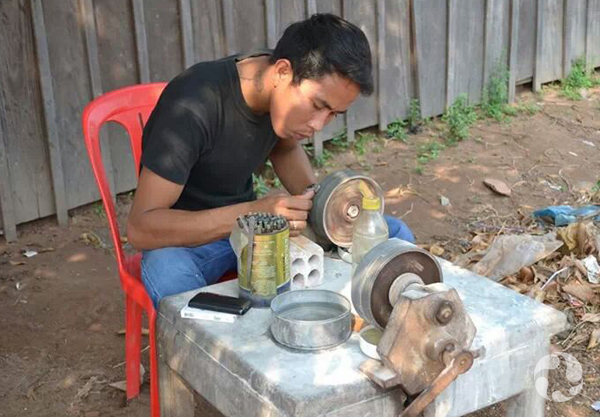 Man sitting outdoors in red chair polishes a zircon using a polishing stone.