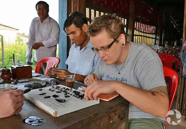 Paula Piilonen and man examine zircons while sitting at table.