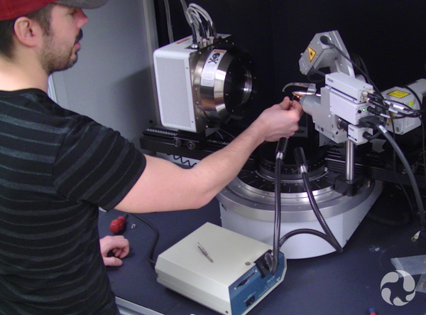 Assistant Ralph Rowe prepares a sample for analysis using the museum's X-ray diffractometer.