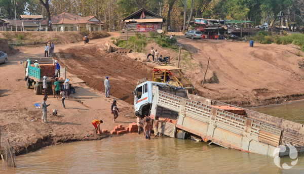 A long truck partially submerged along the bank of the Mekhong River.