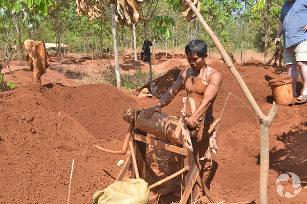 A zircon miner man stands beside a wood machine used to raise buckets from a mine hole.