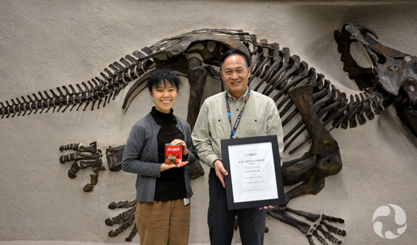 Xiao-chun Wu holds a framed certificate and Tamaki Sato holds a can of tomatoes, in front of a panel-mounted dinosaur skeleton.