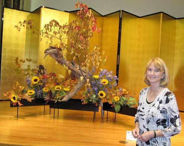 A woman stands beside an ikebana arrangement.