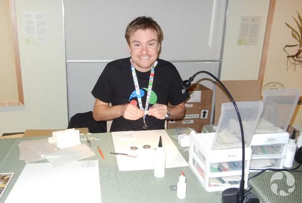 A man sits at a table preparing a herbarium specimen.