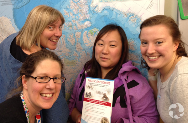 Four women standing before a geographic map of the Arctic hanging on the wall.